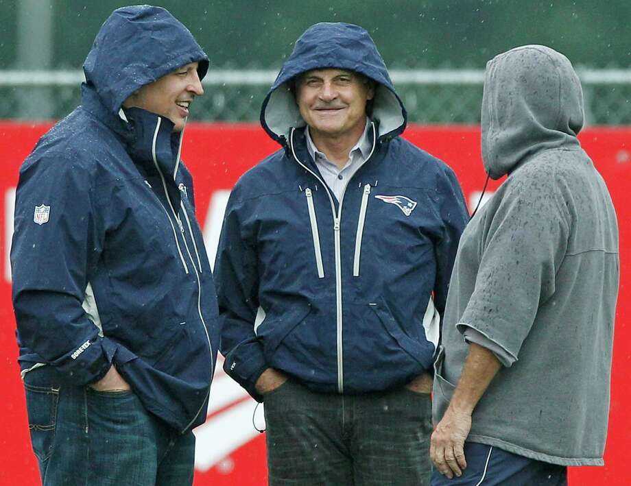 Hoods were needed on a rainy day in Foxborough, Mass., as three sports blended with Chicago Bulls coach Tom Thibodeau, left, and former baseball manager Tony La Russa, center, visiting Bill Belichick at the Patriots' minicamp. Photo: Charles Krupa / AP