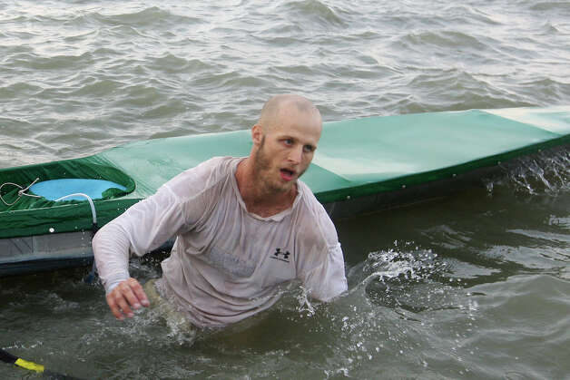 Soloist Kyle Mynar gets off his canoe at the end of the 262-mile 2012 Texas Water Safari canoe race Monday, June 11, 2012. The race starts at Aquarena Springs in San Marcos and ends in Seadrift, by the San Antonio Bay. Mynar was the first men's solo to cross the line and placed 10th place overall. Photo: Jerry Lara, San Antonio Express-News / © 2012 San Antonio Express-News