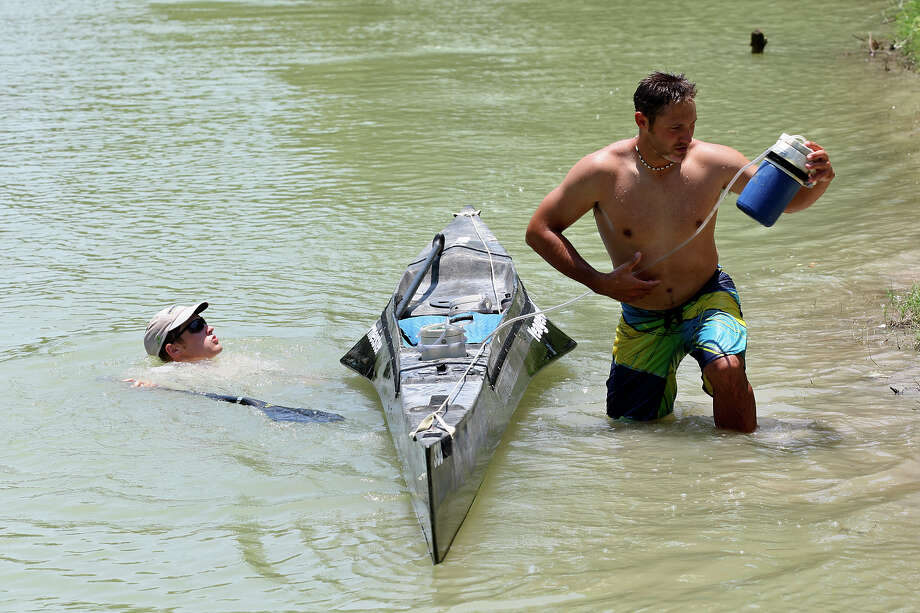 Dodd Yeager cools off in the water as his brother, Coleman Yeager, refreshing his water supply at Checkpoint No. 8 of the 2012 Texas Water Safari canoe race, Sunday, June 10, 2012. The checkpoint is located near Cuero, at the 160 mile marker of the race. Photo: Jerry Lara, San Antonio Express-News / © 2012 San Antonio Express-News