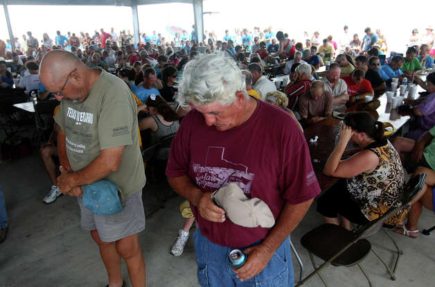 Volunteers Lee Wheelis (left) and Kent Metzler, of Luling, bow their heads in prayer during the 2012 Texas Water Safari awards ceremony at noon in Seadrift, Wednesday, June 13, 2012. A prayer for Brad Ellis, 30, was included during the event. Ellis died Monday afternoon after falling ill during the race early Sunday morning. He died of hyponatremia or low sodium in his system. Photo: Jerry Lara, San Antonio Express-News / © 2012 San Antonio Express-News