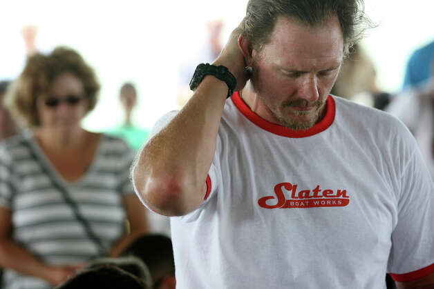 "Jason Rotan bows his head during a prayer at the start of the 2012 Texas Water Safari awards ceremony in Seadrift, Wednesday, June 13, 2012. ""This one is going to hurt,"" he says. A prayer for Brad Ellis, 30, was included during the event. Ellis died Monday afternoon after falling ill during the race early Sunday morning. He died of hyponatremia or low sodium in his system. Photo: Jerry Lara, San Antonio Express-News / © 2012 San Antonio Express-News"