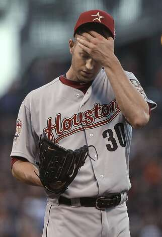Houston Astros pitcher J.A. Happ wipes his face after walking San Francisco Giants' Joaquin Arias during the third inning of a baseball game in San Francisco, Wednesday, June 13, 2012. Photo: Jeff Chiu, Associated Press