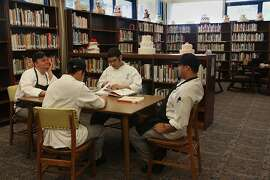 Clockwise from far left--Students Casey Kimmel, Noel A. Franco, Aaron Koga, and Kevin Huang studying for finals at the Alice Statler Library  of the culinary academy of City College of San Francisco in San Francisco, California, tasting wine to differentiate between cabernet, shiraz, and bouchales wine on Thursday, May 17, 2012.