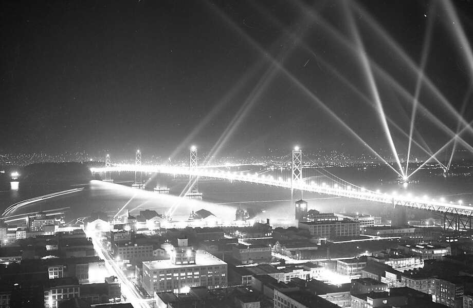 Military ships around the Bay Bridge display lights on opening day. Nov. 11, 1936. Photo: Chronicle File, The Chronicle