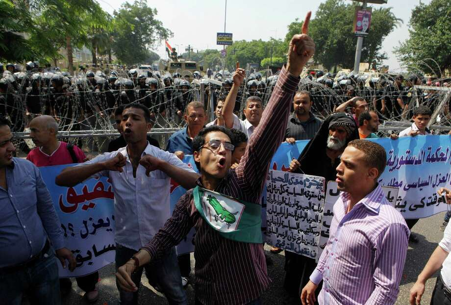 "Egyptian protesters shout anti-military rule slogans during a protest in front of soldiers guarding in front of Egypt's highest court - the Supreme Constitutional Court – in Cairo, Egypt, Thursday June 14, 2012. The court will decide whether Shafiq, Mubarak's last prime minister before he was ousted in February 2011, can stay in the race or not. The court is to rule on the validity of a ""political exclusion"" law passed by parliament barring many former regime figures from running for office. Arabic read ""who worked with Mubarak's regime should be executed from his political rights"".  (AP Photo/Amr Nabil) Photo: Amr Nabil"