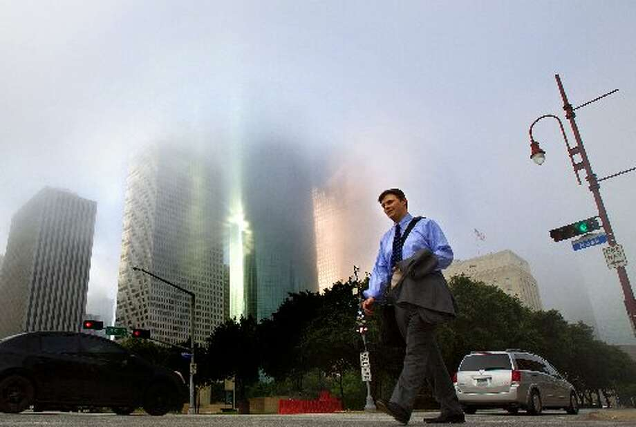 Fog looms over downtown as Zach Loney crosses Rusk Street Wednesday, June 13, 2012, in Houston. (Cody Duty / Houston Chronicle)