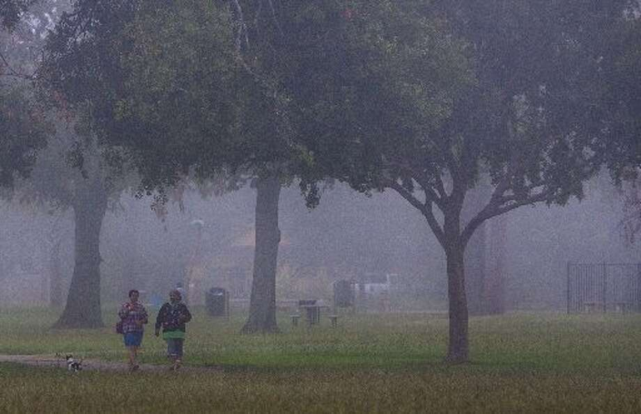Fog looms as patrons walk through Montie Beach Park Wednesday, June 13, 2012, in Houston. (Cody Duty