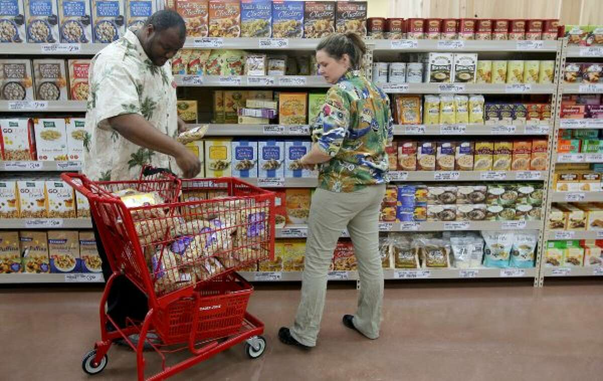 Employees Larry Givens and Megan Hershfeld stock shelves at Trader Joe's at the Woodlands Crossing Shopping Center in The Woodlands. (Thomas B. Shea / For the Chronicle)