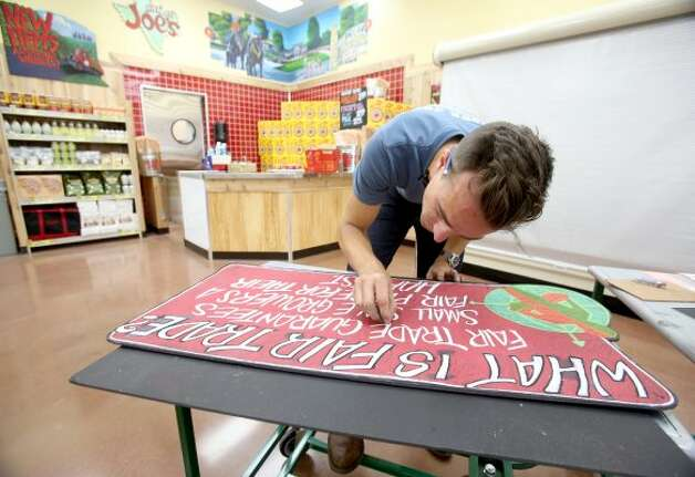 Artist Will Pierce works on a sign at the first Trader Joe's in Houston, which opens Friday, June 15, 2012, at the Woodlands Crossing Shopping Center in The Woodlands. (Thomas B. Shea / For the Chronicle)