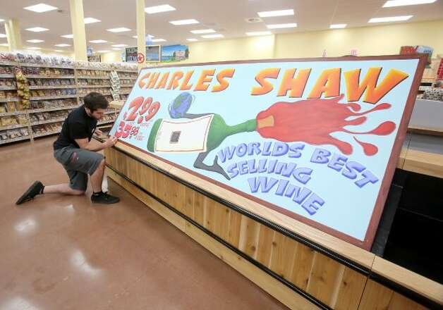 Artist Lucas Weaverling works on a Charles Shaw wine sign at the first Trader Joe's in Houston, which opens Friday, June 15, 2012, at the Woodlands Crossing Shopping Center in The Woodlands. (Thomas B. Shea / For the Chronicle)