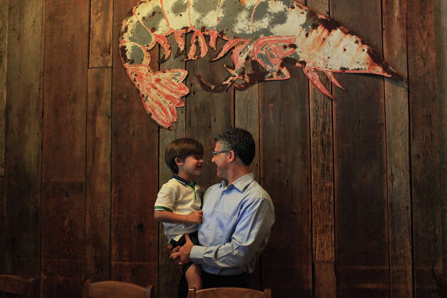 Barclay Anthony talks with his son, Beau, 5, at their family's restaurant, Sea Island Shrimp House. Photo: Lisa Krantz, San Antonio Express-News / 2012 San Antonio Express-News
