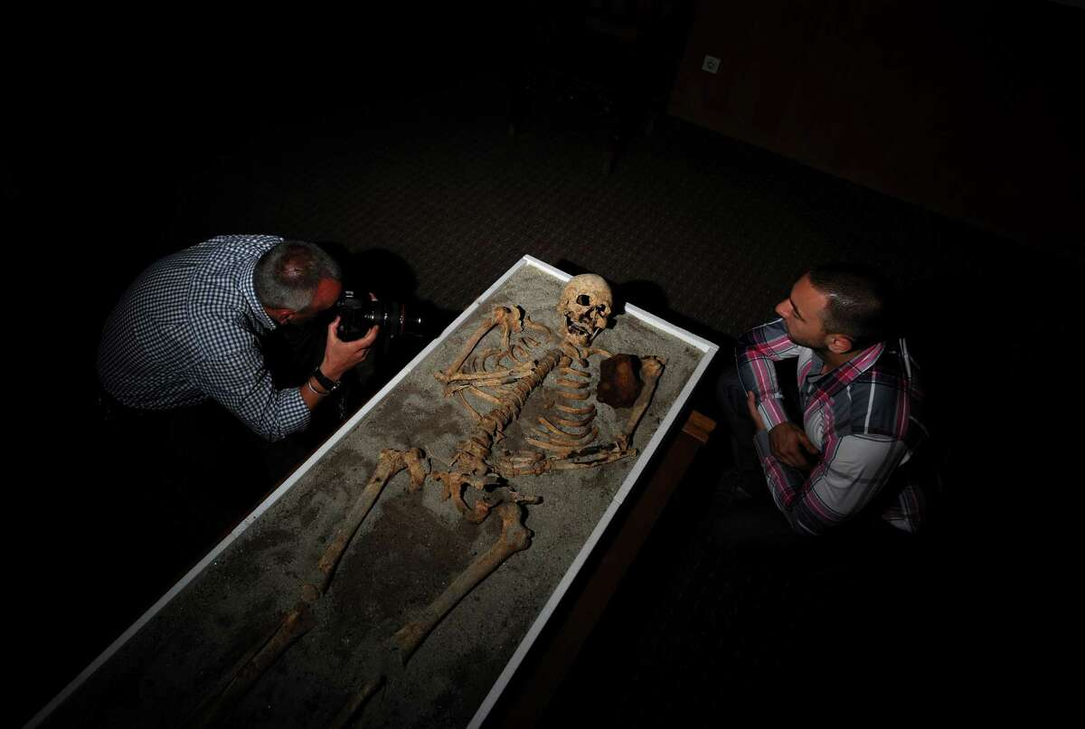 Journalists examine a skeleton with an iron piece during a news conference at the National History museum in Sofia on Thursday. The ancient skeleton of a man, pinned down in his grave in order not to turn into a vampire, piqued interest in Bulgaria this week, where vampire tales and rites still keep their bite even nowadays. The 700-year-old skeleton -- unearthed near a church in the Black Sea town of Sozopol earlier in June -- was stabbed in the chest with an iron rod and had his teeth pulled before being put to rest. ( NIKOLAY DOYCHINOV/AFP/GettyImages)