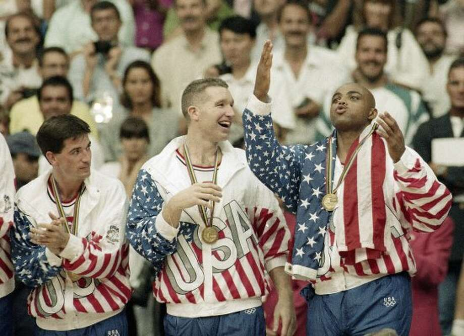 FILE - In this Aug. 8, 1992, file photo, From left the USA's John Stockton, Chris Mullin, and Charles Barkley rejoice with their gold medals after beating Croatia 117-85 in the gold medal game in men's basketball at the Summer Olympics in Barcelona. It's not an urban legend: The Dream Team really did lose a scrimmage to a group of college stars as the future Hall of Famers prepared for the 1992 Olympics. Footage of that game is among the new behind-the-scenes material in the 20-year anniversary documentary that premieres on NBA TV on Wednesday. (AP Photo/John Gaps III, File) (AP)