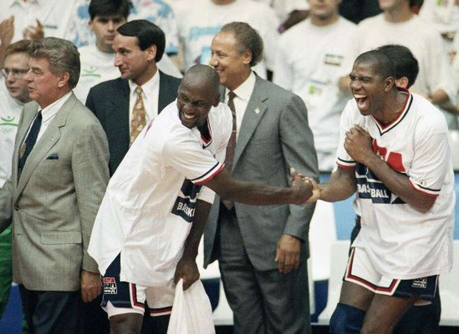 "FILE - In this Aug. 8, 1992, file photo, USA's Earvin ""Magic"" Johnson, right, and Michael Jordan shake hands near the end of their 117-85 win over Croatia in the gold medal game in men's basketball at the Summer Olympics in Barcelona. Head coach Chuck Daly, left, and his assistant coaches Mike Krzyzewski, second left, and Lenny Wilkens, center, look on  It's not an urban legend: The Dream Team really did lose a scrimmage to a group of college stars as the future Hall of Famers prepared for the 1992 Olympics. Footage of that game is among the new behind-the-scenes material in the 20-year anniversary documentary that premieres on NBA TV on Wednesday.(AP Photo/John Gaps) (AP)"