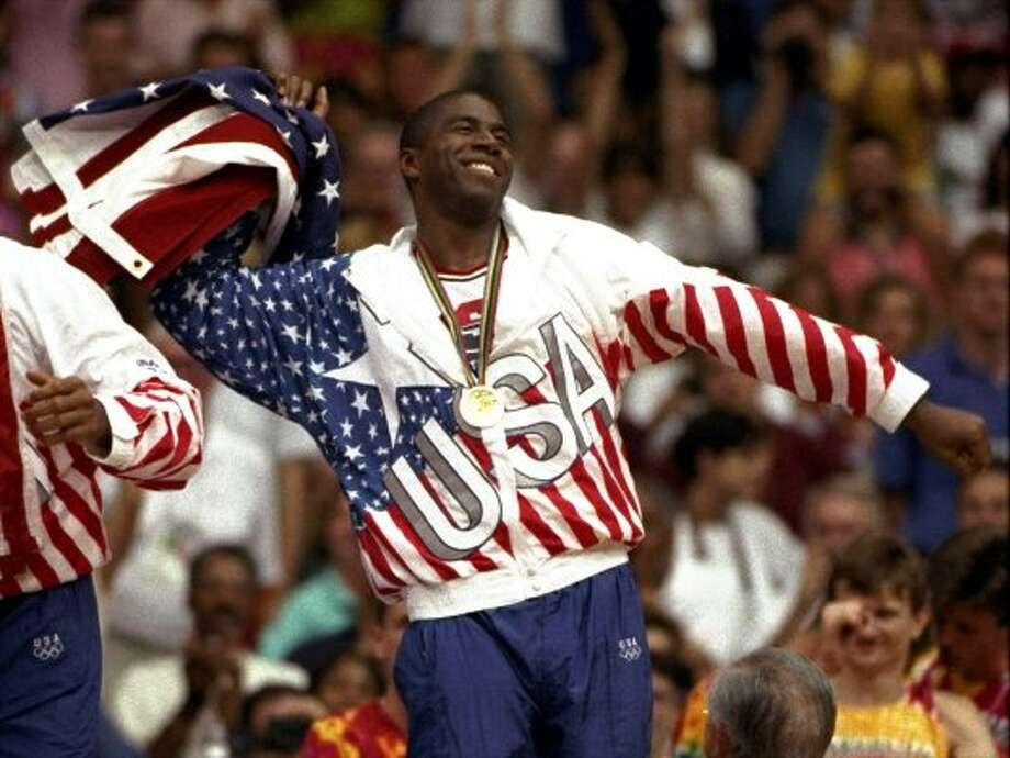 "USA's Earvin ""Magic"" Johnson whips the United States flag in ecstasy during the gold medal ceremony Saturday, August 8, 1992,  during the 1992 Summer Olympic games in Barcelona. (AP Photo/ Susan Ragan) (AP)"