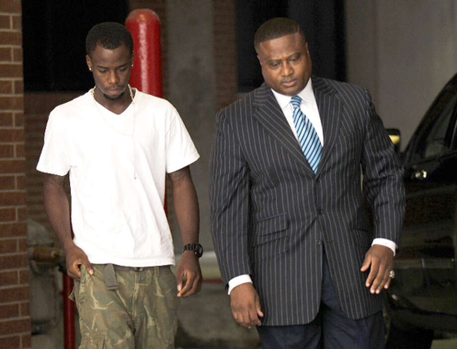 Chad Holley, left, walks out of the Harris County Jail with activist Quanell X after posting bail on a burglary charge Thursday, June 14, 2012, in Houston. Photo: (Brett Coomer / Chronicle)