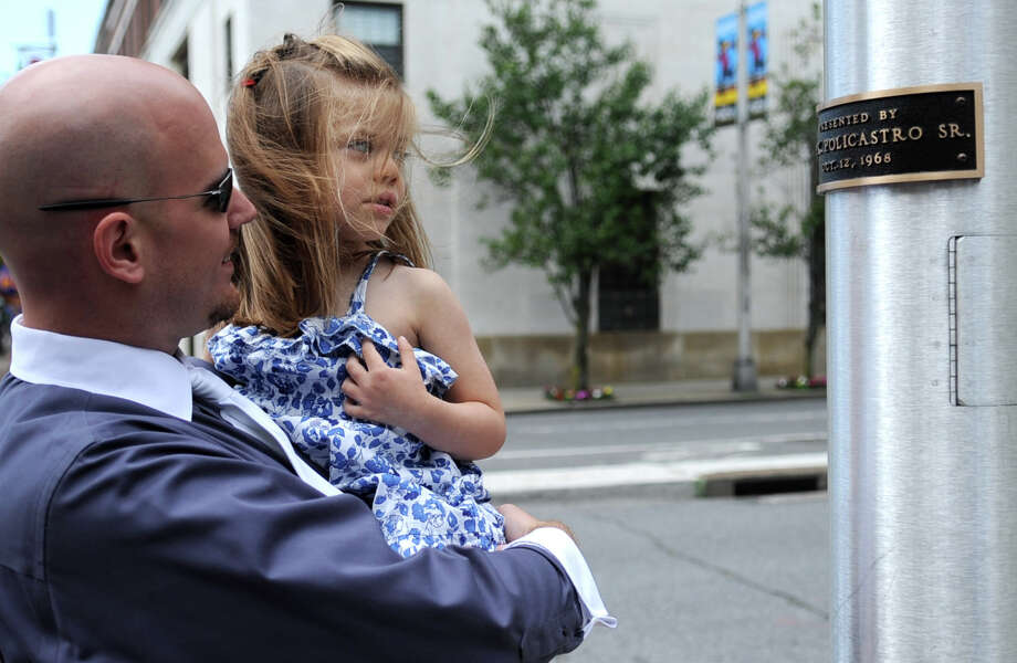 Francis Peter Policastro IV shows his niece, Isabella Ortegon, 4, the plaque with his great-grandfathers name attached to the flagpole during a dedication ceremony at One Public Library Plaza in front of the Ferguson Library on Thursday, June 14, 2012. The flagpole replaces the original one which was hit by a car. The original was donated by Frank Policastro Sr. in 1968. Photo: Lindsay Niegelberg / Stamford Advocate