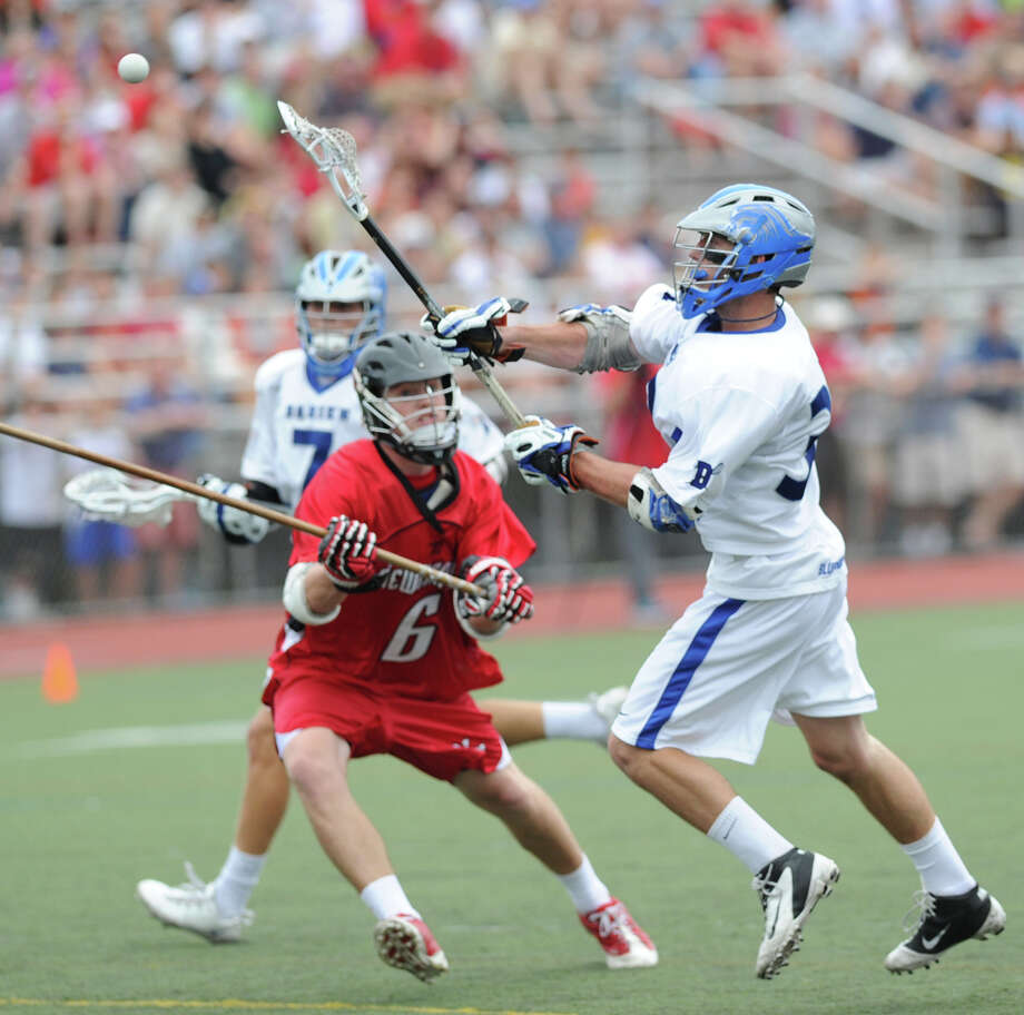 At right, Darien's Henry West, scores his team's 10th goal while being defended by New Canaan's Hunter Budd # 6, during the class M Boys Lacrosse championship game between Darien High School and New Canaan High School at Brien McMahon Hgh School in Norwalk, Saturday, June 9, 2012. Darien won the championship 11-5. Photo: Bob Luckey / Greenwich Time