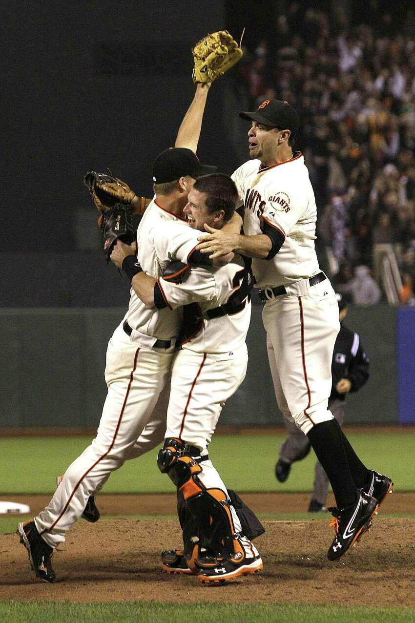 San Francisco Giants pitcher Matt Cain, left, celebrates with catcher Buster Posey, center, and first baseman Brandon Belt after the final out of the ninth inning of a baseball game against the Houston Astros in San Francisco, Wednesday, June 13, 2012. Cain pitched the 22nd perfect game in major league history and first for the Giants, striking out a career-high 14 and getting help from two spectacular catches to beat the Houston Astros 10-0. (AP Photo/Jeff Chiu)