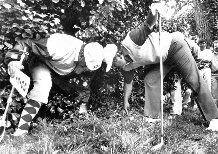 Lee Trevino, right, and a marshal clear leaves away from the ball after Trevino's shot landed in the brush on the 6th hole on June 18, 1987. Trevino took a double bogey 6 on the hole. UPI/Blake Sell Photo: Blake Sell, UPI