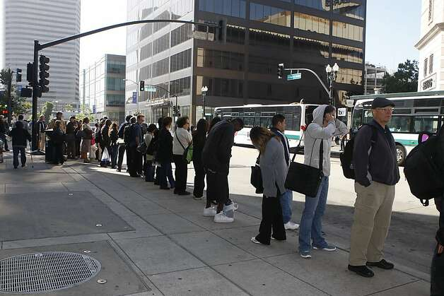 Commuters waited in long lines on 20th St. at Broadway in Oakland, California, after an early morning fire halted transbay service on Thursday, June 14, 2012.  A section of the third rail at BART's west oakland station were damaged as crews work to replace it. Photo: Liz Hafalia, The Chronicle