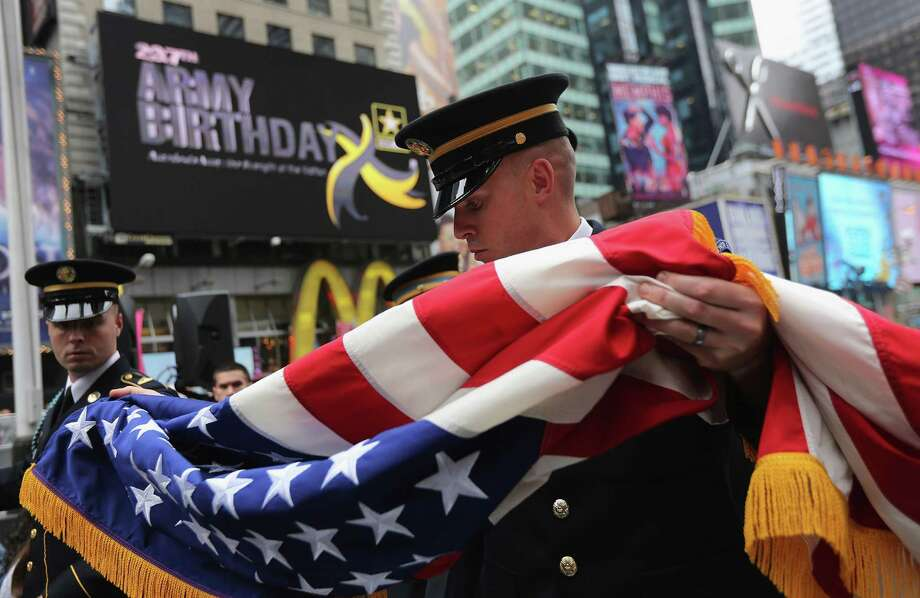 NEW YORK, NY - JUNE 14:  U.S. Army soldiers fold the U.S. flag after an event in Times Square marking the Army's 237th anniversary on June 14, 2012 in New York City. U.S. Army Chief of Staff Gen. Raymond Odierno swore in 16 new recruits during the celebration. Photo: John Moore, Getty Images / 2012 Getty Images