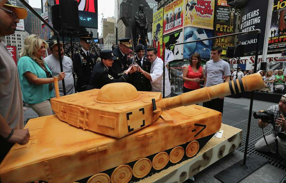 U.S. Army Chief of Staff Gen. Raymond Odierno cuts a cake marking the Army's 237th anniversary on June 14, 2012 in Times Square in New York City. Odierno was joined by fellow Army troops as he swore in 16 new recruits in a ceremony celebrating the Army's birthday. ''Cake Boss'' reality show Buddy Valastro (R), helped Odierno cut the 500 pound cake in the shape of a tank, which Valastro said took 8 of his staff three days to prepare for the event. Photo: John Moore, Getty Images / 2012 Getty Images