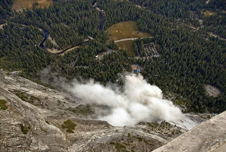 FILE - In this Oct. 8, 2008, file photo, a dust cloud is seen from the Glacier Point overlook during a rock fall that damaged lodging facilities at Curry Village in Yosemite National Park, Calif. Falling boulders are the single biggest force shaping Yosemite Valley, one of the most popular tourist destinations in the nation's system of national parks. Now large swaths of popular haunts deemed unsafe are closing as officials acknowledge they knew for more than a decade ago that unsuspecting tourists were being lodged in harm's way. On Thursday, June 14, 2012,  the National Park Service will announce that potential danger from the unstable 3,000-foot-tall slab of granite known as Glacier Point, a picturesque promontory that for decades has provided a dramatic backdrop to park entertainment events, will leave uninhabitable large parts of Yosemite Valley's most popular lodging areas. (AP Photo/Jim Nichols, File) Photo: Jim Nichols, Associated Press