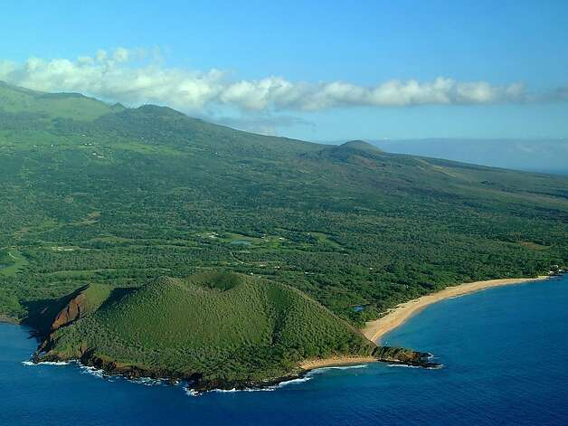 "This aerial view of Makena State Park, shows Oneloa and Pu'u Ola'i beaches, more commonly known as ""Big Beach"" and ""Little Beach,"" during a verdant period, most likely winter or spring. The cinder cone and surrounding landscape reveal more reds and browns in summer and fall. Photo: Ron Garnett, HTA"