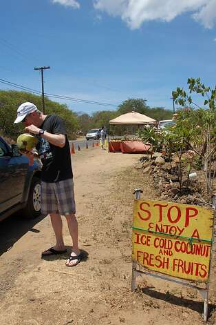 The original form of coconut water, enjoyed by the side of the road in Makena, helps a visitor rehydrate after a hot, dusty walk from the area's only resort to the state park famed for its beaches. Photo: Jeanne Cooper, Special To SFGate