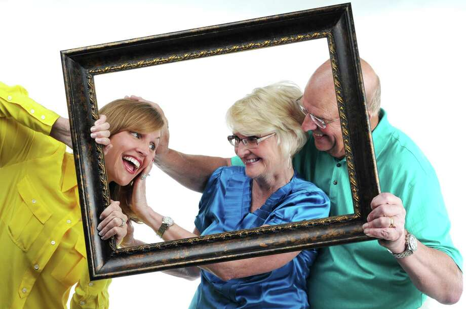Photo illustration showing Kristi Gustafson Barlette, left, being pushed out of a picture frame held by her parents, Lynn and Peter Gustafson, right, Friday June 8, 2012. (Will Waldron / Times Union photo illustration)