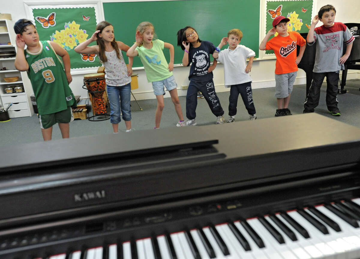 Noel Liberty teaches music lessons to students at The Music Studio June 6, 2012 in Colonie, N.Y. The students are, from left, Jacob Oliver, 7, Sinead FitzPatrick, 7, Gabrielle Rychcik, 8, Isabella Fuierer, 8, Nicholas Fuierer, 7, Nick Watson, 9, and R.J. Burkitt, 9. (Lori Van Buren / Times Union)