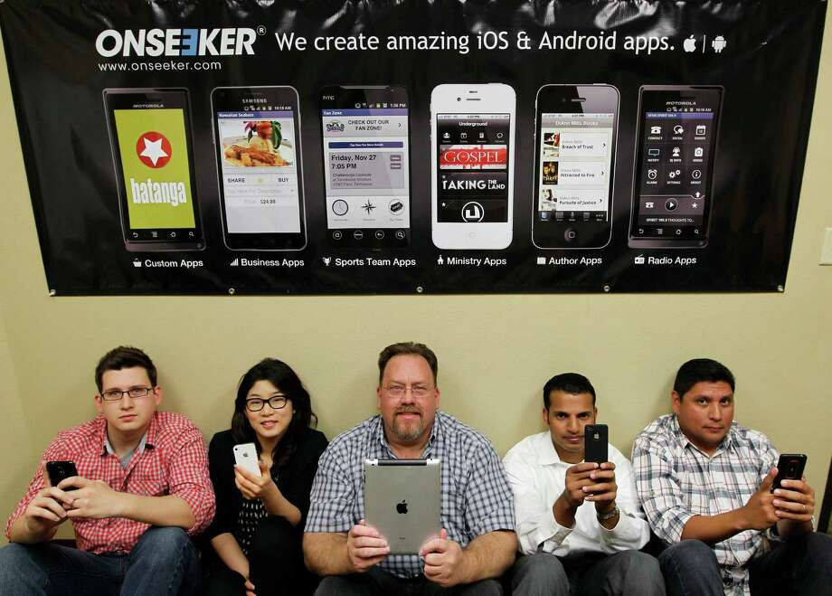 Onseeker director of communications Frank Danna, from left, graphic designer Jee Youn, CEO Charles Danna, chief technology officer Mohammad Anwar and COO Roy Gonzalez work for the Houston company that develops iPhone and Android apps for churches and other businesses. Photo: James Nielsen / © Houston Chronicle 2012