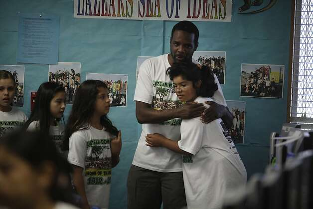 Lazear Elementary School principal Kareem Weaver (second from right) gives a hug of support to Ali Nevarez (right) as fourth graders prepare to take a reading test  on Wednesday, June 13, 2012 in Oakland, Calif. Photo: Lea Suzuki, The Chronicle