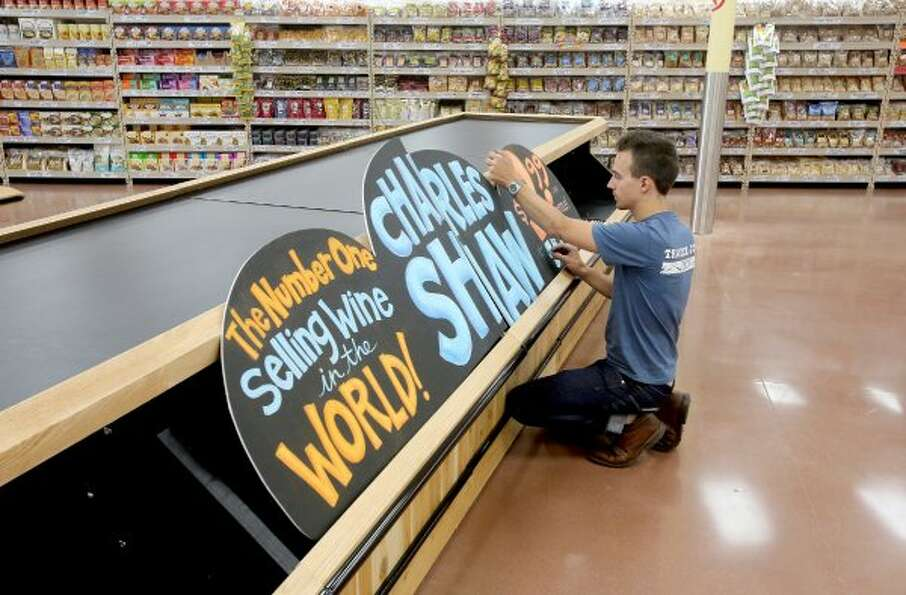 Artist Will Pierce works on a Charles Shaw wine sign at the first Trader Joe's in Houston, which ope