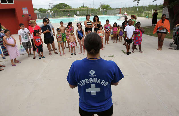 Lifeguard and swim instructor Jade Feuge (front) gathers about 35 swimmers in preparation to set a record for the largest swimming lesson on Thursday, June 14, 2012. City of San Antonio's Parks and Recreation department joined other organizations in an attempt to set a record for the world's largest swimming lesson.  The department held swimming lessons across all city swimming pools. Instructors gave free swim lessons for about one hour. Although the idea of setting a world record was the catalyst for the event, the main theme was to teach about swimming safety according to Parks and Recreation spokesperson Lyn Kinton. The summer swimming season kicks off on Saturday where all city pools will be open every day except for Mondays from 1 to 7 p.m. Photo: Kin Man Hui, San Antonio Express-News / @2012 San Antonio Express-News