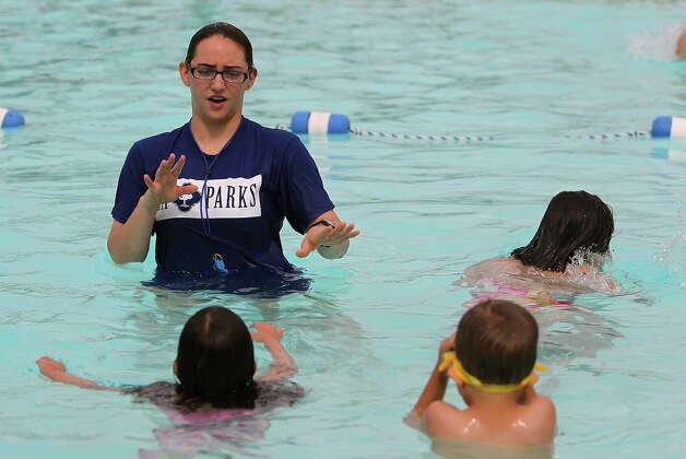 Lifeguard and swim instructor Jade Feuge helps younger swimmers with a lesson at Lady Bird Johnson Park's swimming pool on Thursday, June 14, 2012. The City of San Antonio's Parks and Recreation department joined other organizations in an attempt to set a record for the world's largest swimming lesson. The department held swimming lessons across all city swimming pools. Instructors gave free swim lessons for about one hour. Although the idea of setting a world record was the catalyst for the event, the main idea was to teach about swimming safety according to Parks and Recreation spokesperson Lyn Kinton. The summer swimming season kicks off on Saturday where all city pools will be open every day except for Mondays from 1 to 7 p.m. Photo: Kin Man Hui, San Antonio Express-News / @2012 San Antonio Express-News