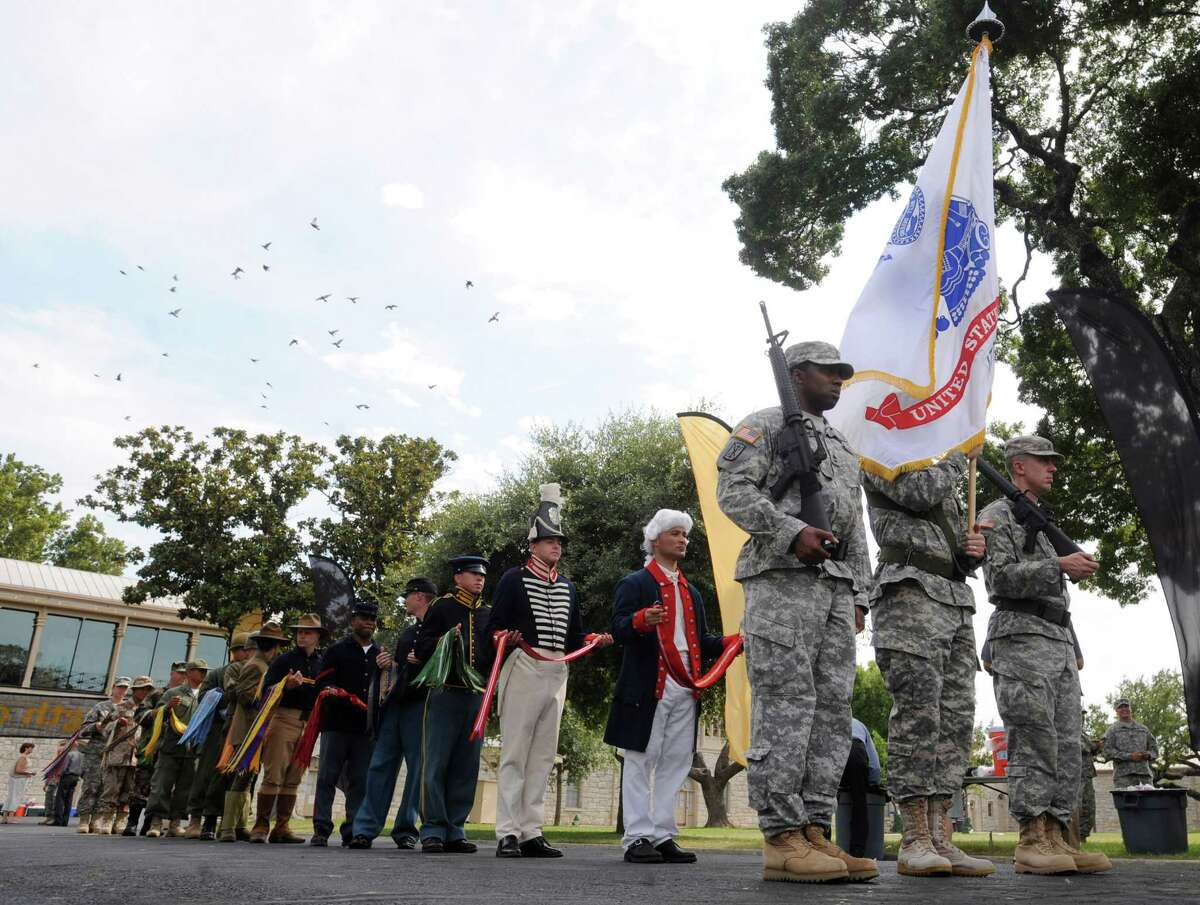Soldiers carry the Army flag as others wearing period uniform from the Revolutionary War to the present day line up behind them during a celebration of the Army's 237th birthday and Flag Day at the Fort Sam Houston Quadrangle on Thursday, June 14, 2012.