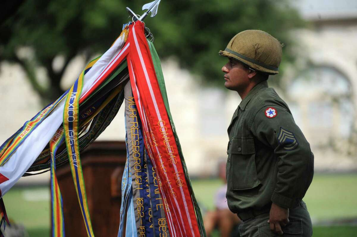 Spc. Juan Perez wears a Korean War-era uniform after attaching battle ribbons to the Army flag during a celebration of the Army's 237th birthday and Flag Day at the Fort Sam Houston Quadrangle on Thursday, June 14, 2012.