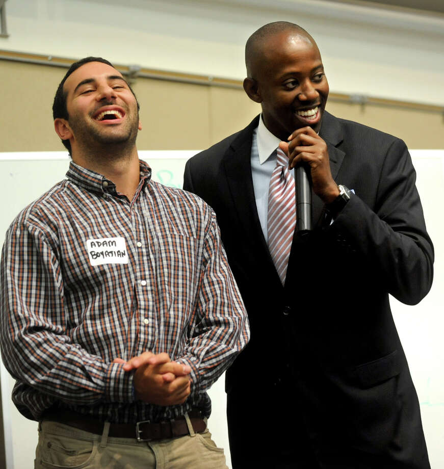 Adam Boyajian, left, laughs after being told he won $1000 prize in a white-board challenge during the 5th annual career expo held by the Westchester/Greater Connecticut chapter of the National Black MBA Association at UConn Stamford on Thursday, June 14, 2012. The award was presented by chapter membership chair George Boyce, right, and supplied by sponsor Community Bank of Bridgeport. Boyajian's idea involves bridging the gap between bus companies and college campuses with little to no public transportation options. Photo: Lindsay Niegelberg / Stamford Advocate