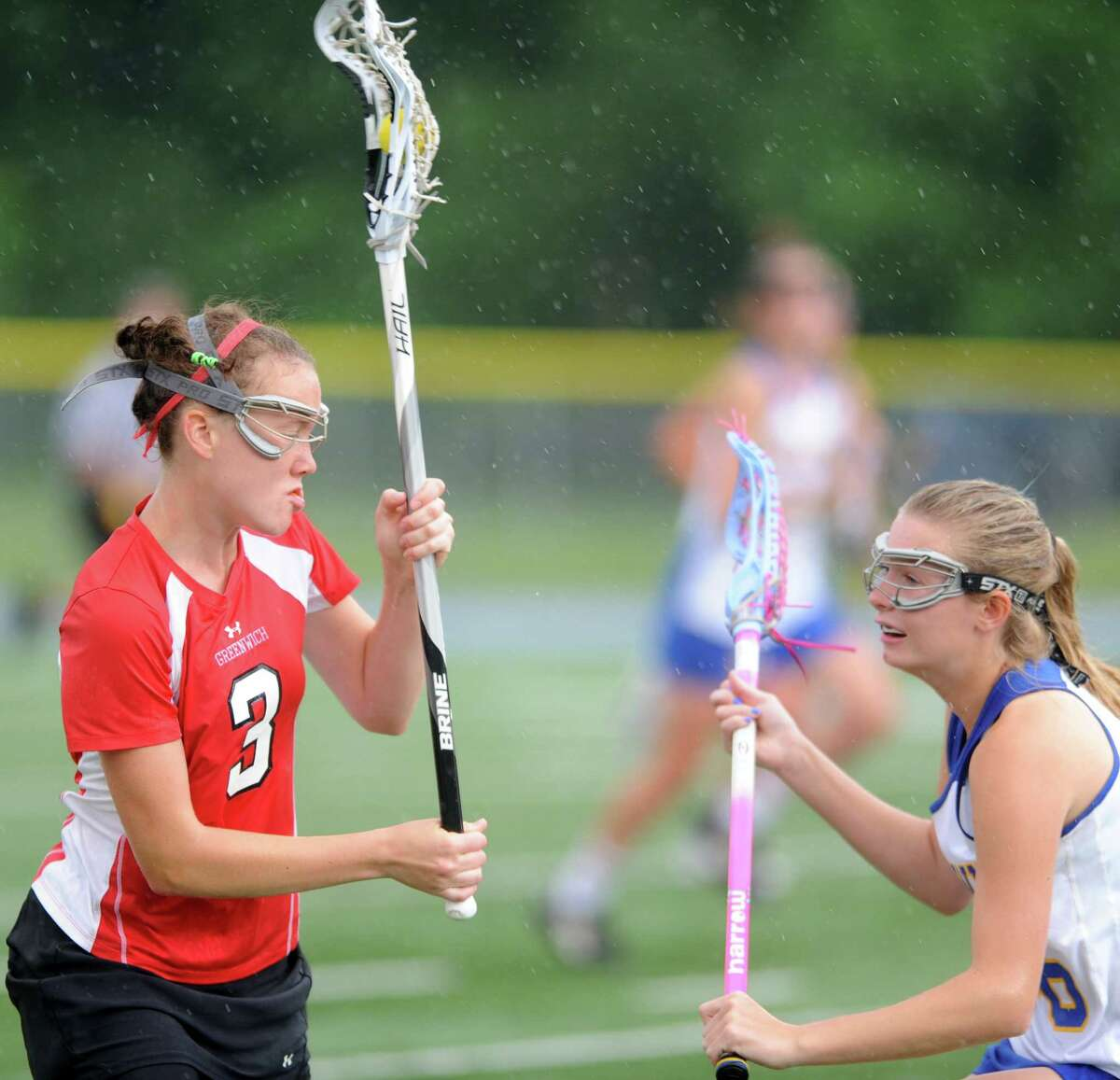 Greenwich's Claire Feeney controls the ball as Newtown's Kaitlyn VosWinkle defends during the Girls Lacrosse State Tournament Class L Semifinals Wednesday, June 6, 2012 at Bunnell High School in Stratford, Conn.