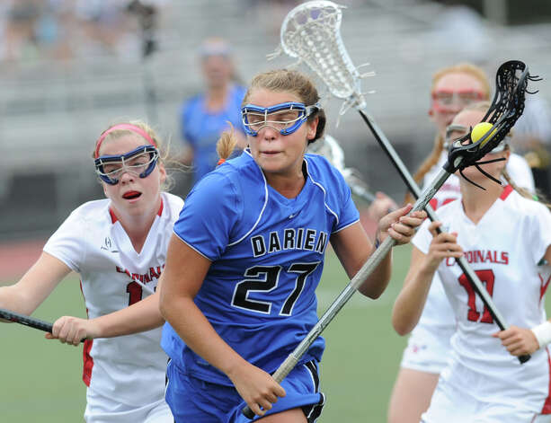 Taylor Hardison, center, # 27 of Darien, gets past Sophia Waine, right,  # 17 of Greenwich, during the FCIAC girls lacrosse finals between Greenwich High School and Darien High School at Brien McMahon High School in Norwalk, Friday, May 25, 2012. Darien won the championship over Greenwich 17-14. Photo: Bob Luckey / Greenwich Time