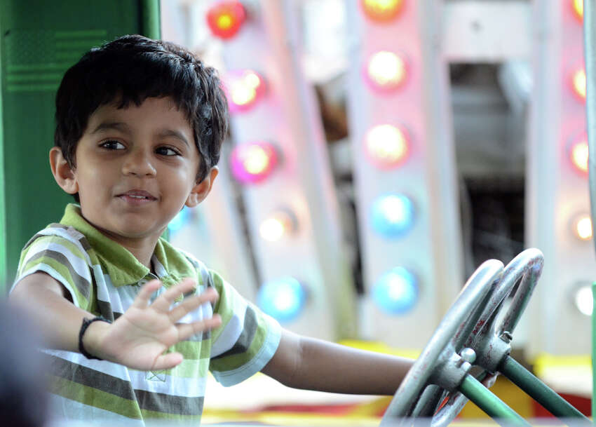 Sriram Guni, 4, of Stamford, waves to his family as he rides in a car during the First Presbyterian Church's first carnival fundraiser in Stamford on Thursday, June 14, 2012.
