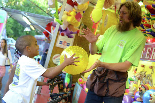 Andrew Gullans, of Savin Rock Amusements, awards Marcus Watts, 7, of Stamford, a prize for winning the Balloon Water Race game during the First Presbyterian Church's first carnival fundraiser in Stamford on Thursday, June 14, 2012.