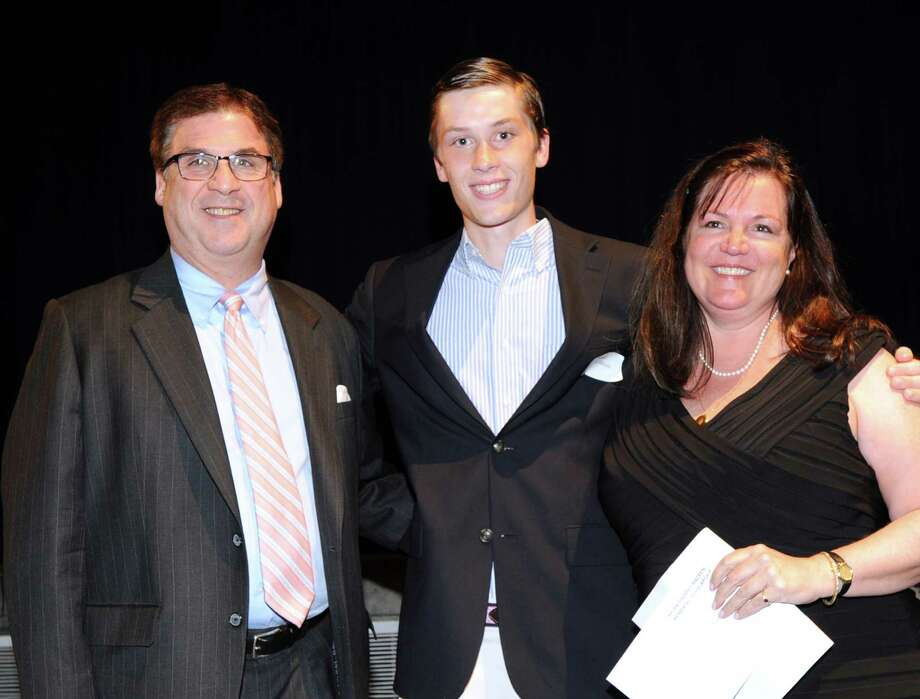 Ryan Corrigan, center, a senior at Greenwich High School, is awarded the Brian Thomas Macken Memorial Scholarship by Tom and Laura Macken, husband and wife, during the Greenwich Scholarship Association's 40th annual scholarship evening at Greenwich High School, Thursday, June 14, 2012. The GSA awarded scholarships to 126 recipients, said Dr. Marie Hertzig, the president of the organization. Photo: Bob Luckey / Greenwich Time