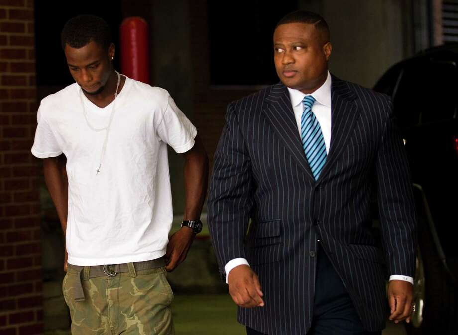 Chad Holley leaves the Harris County Jail on Thursday with activist Quanell X after posting $10,000 bail. Holley was arrested Wednesday after a home burglary was reported. Photo: Brett Coomer / © 2012 Houston Chronicle