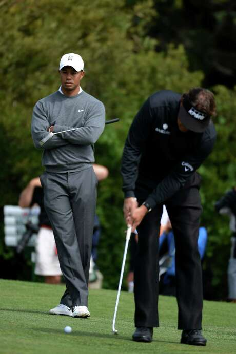 SAN FRANCISCO, CA - JUNE 14:  Phil Mickelson of the United States hits a putt on the first hole as Tiger Woods looks on during the first round of the 112th U.S. Open at The Olympic Club on June 14, 2012 in San Francisco, California. Photo: Harry How, Getty Images / 2012 Getty Images