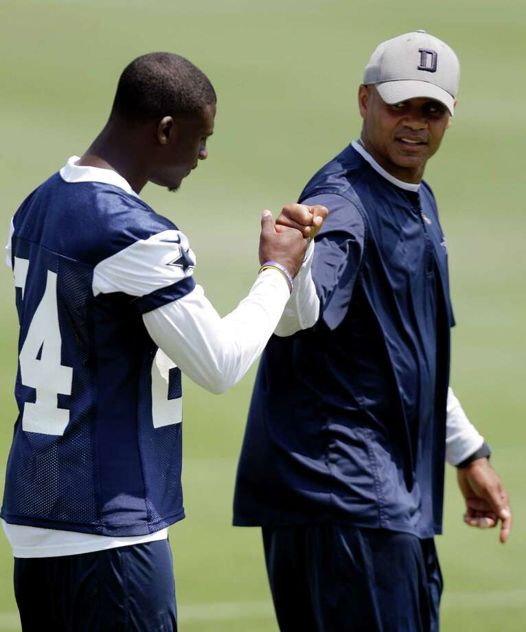 Dallas Cowboys cornerback Morris Claiborne (left) gets a fist bump from secondary coach Jerome Henderson following a morning workout earlier this month in Irving. Photo: Tony Gutierrez, Associated Press