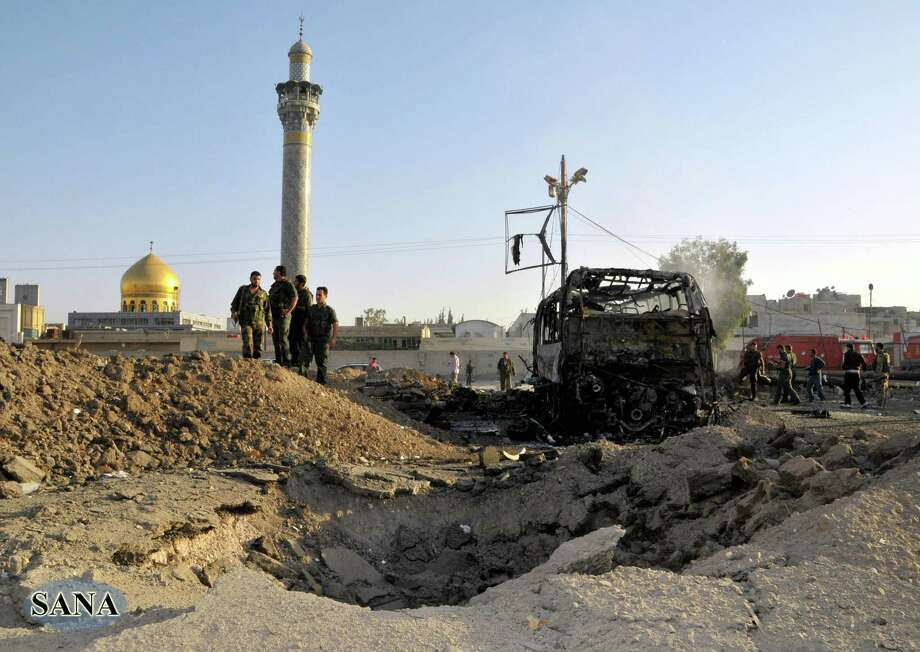 In this photo released by the Syrian official news agency SANA, Syrian soldiers stand at the explosion site where a car bomb exploded near the shrine of Sayyida Zeinab, seen in the background, suburb of Damascus, Syria, Thursday, June 14, 2012. A car bomb exploded Thursday in a Damascus suburb that is home to a popular Shiite Muslim shrine, wounding at least two people, Syria's state-run news agency SANA reported, while activists said regime troops continued shelling rebellious areas in central Homs province. (AP Photo/SANA) Photo: Anonymous