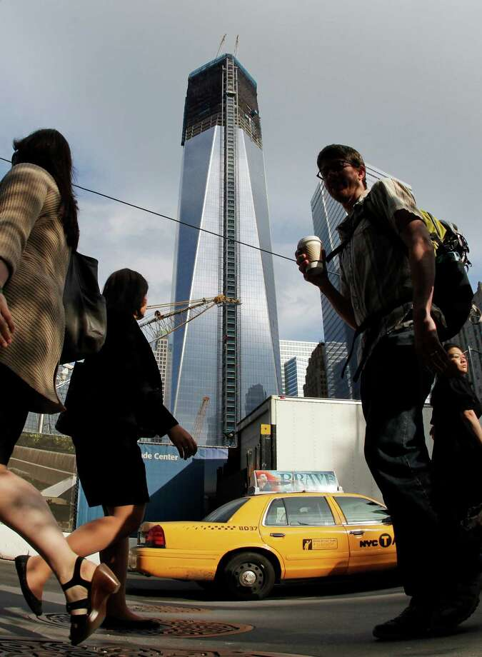Commuters walk past the World Trade Center construction site and One World Trade Center, center, Thursday, June 14, 2012 in New York.  President Barack Obama is scheduled to visit the site later Thursday. World Trade Center PATH service will be suspended during Obama's visit and PATH trains from Newark will terminate at Grove Street in Jersey City.(AP Photo/Mark Lennihan) Photo: Mark Lennihan